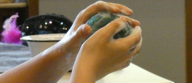 Hände kneten einen Filzball