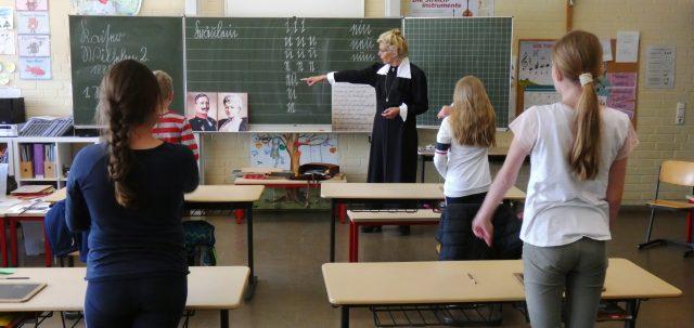 Fräulein Lehrerin steht an der Tafel und erklärt den Kinder die damalige Schreibschrift. Außerschulisches Lernen in der Schule.