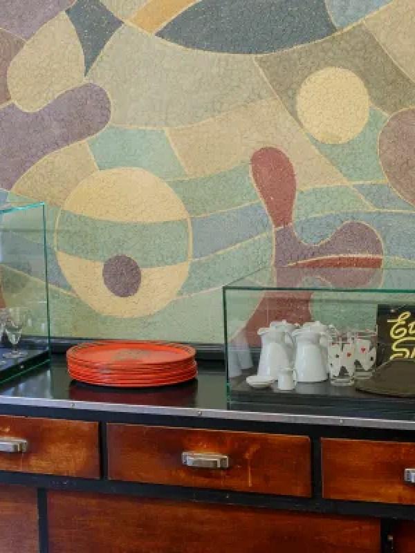 Theke mit Holztäfelung, hinter der Theke abstraktes Wandgemälde