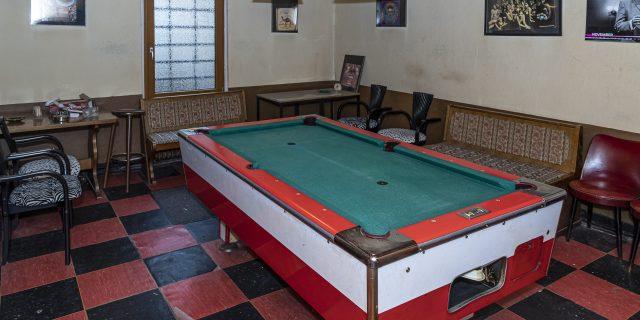 Raum mit Schachbrettfliesen in rot und schwarz, darauf ein großer Billardtisch