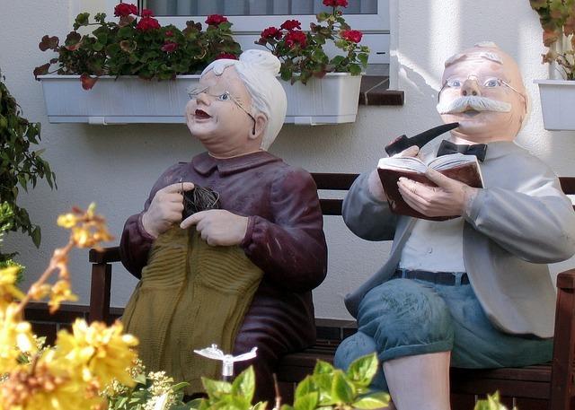 Oldies, Oma strickt und Opa liest auf der Gartenbank.