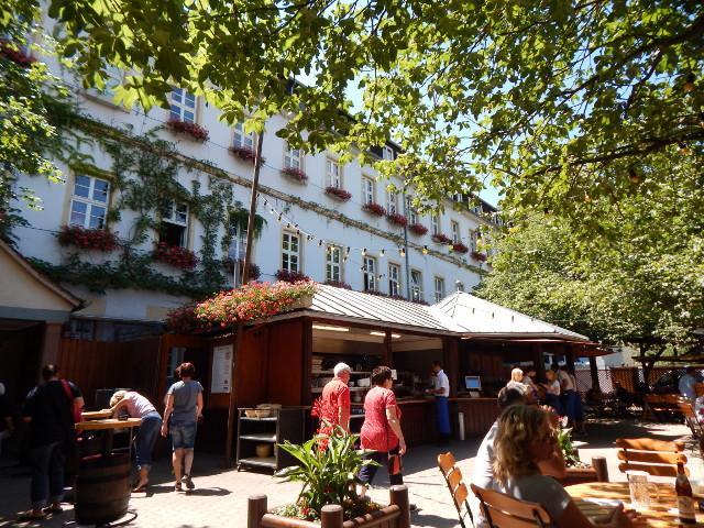 Der Domhof Biergarten in Speyer, gebießen unter schattigen Bäumen.