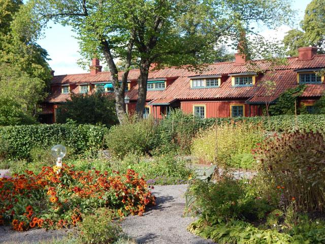 Bunte Bauern- und Kräutergärten vor rotem Holzhaus.