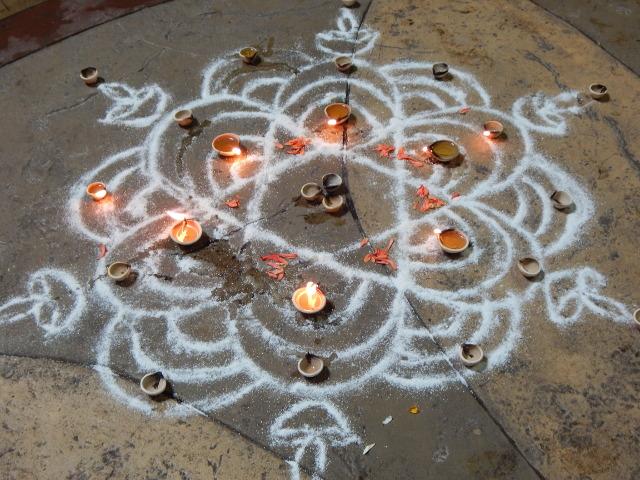 Am Boden der Batu Caves ist ein Mandala mit Öllämpchen gezeichnet.