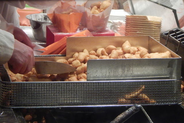 Das leckere Schmalzgebäck auf dem Weihnachtsmarkt in Hamburg wird frisch gebacken.