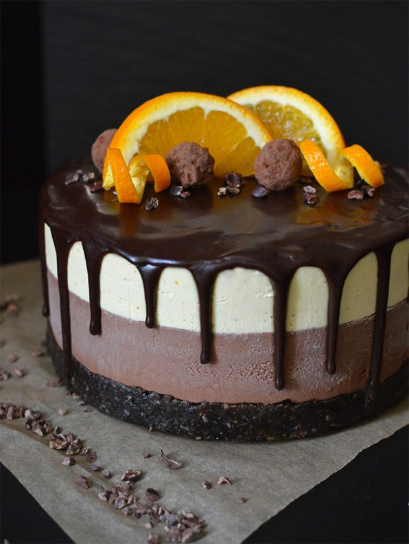 Raw double chocolate orange cheesecake, with a chewy brownie base, rich chocolate cheesecake, and a fresh, zingy orange cheesecake layer, topped with a dark, chocolate sauce.