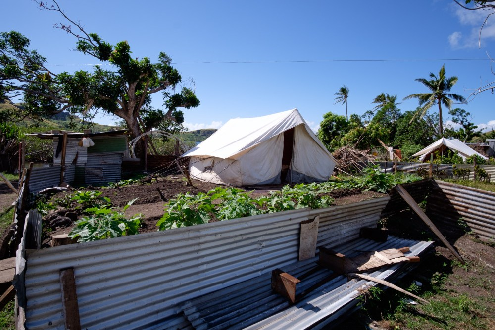 Temporary shelter and a garden on the foundations of a former house in Saioko village, Ra