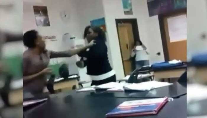 Cell phone footage from a student captured a fight between a student and a teacher in a seventh-grade classroom. (Source: WXYZ/cell phone video/CNN)