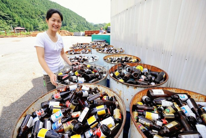 Sonae Fujii of the Zero Waste Academy in Kamikatsu stands next to containers filled with waste ready for recycling at the Hibigaya Waste Station in central KamikatsuTown in Shikoku, Japan on July 22, 2008. Photographer: Robert Gilhooly