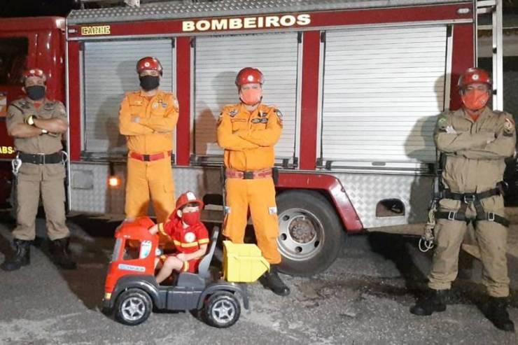 criança em frente caminhão bombeiros