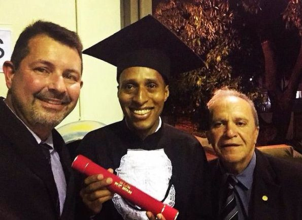 Formando de beca e canudo na mão com outros dois homens sorrindo para selfie