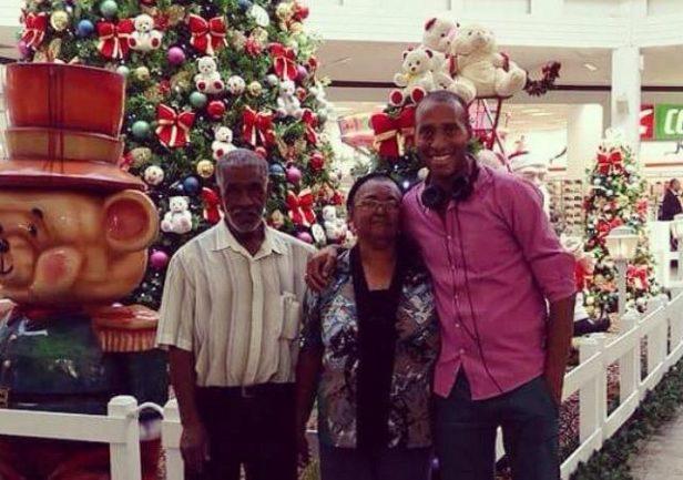 Filho com pai e mãe em decoração natalina de shopping