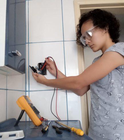 Mulher fazendo serviço de elétrica em parede