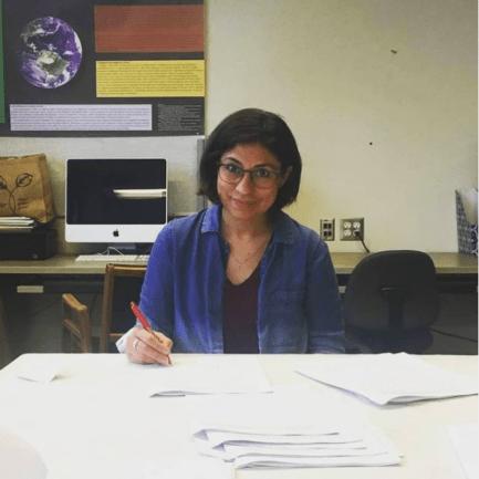 Pesquisadora que venceu prêmio sentada em mesa, escrevendo com computador na mesa de trás