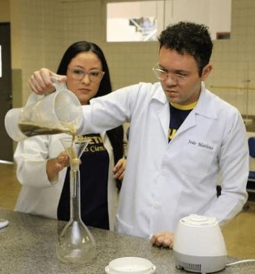 Estudante e professora em laboratório colocando liquidificador com extrato do pequi em reservatório