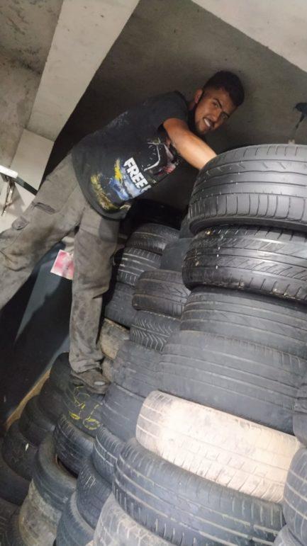 Homem entre pneus em borracharia