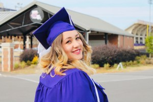 Beautiful woman smiling over her shoulder wearing cap and gown