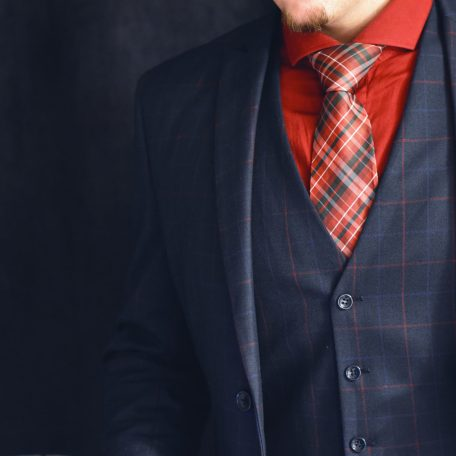 Plaid red tie in blue suit and blue paisley pocket square