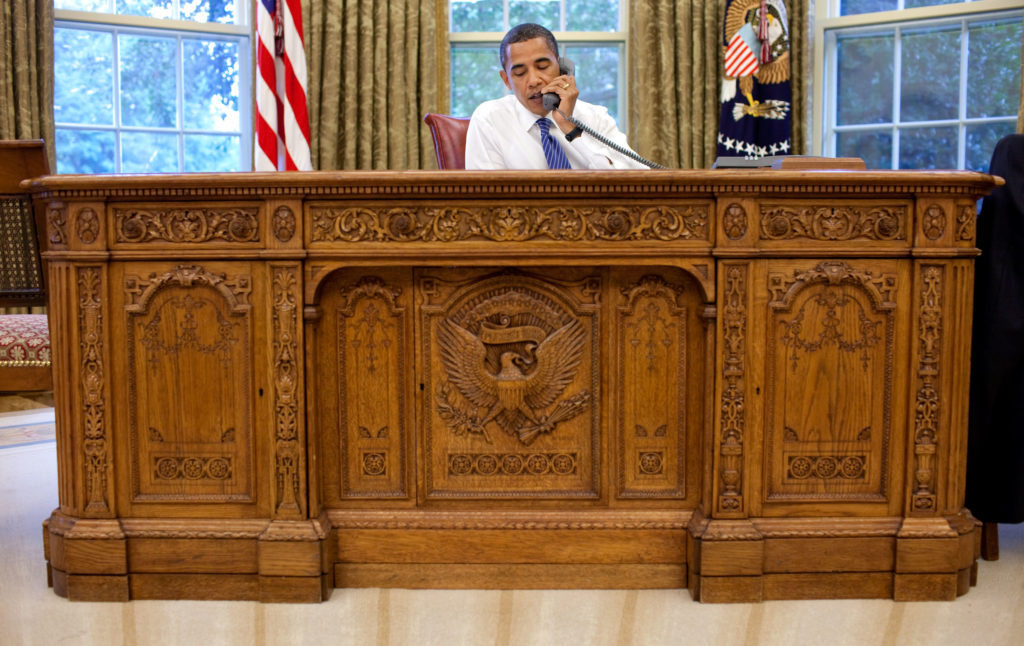 President Barack Obama takes a conference call while sitting behind the Resolute Desk in the Oval Office.