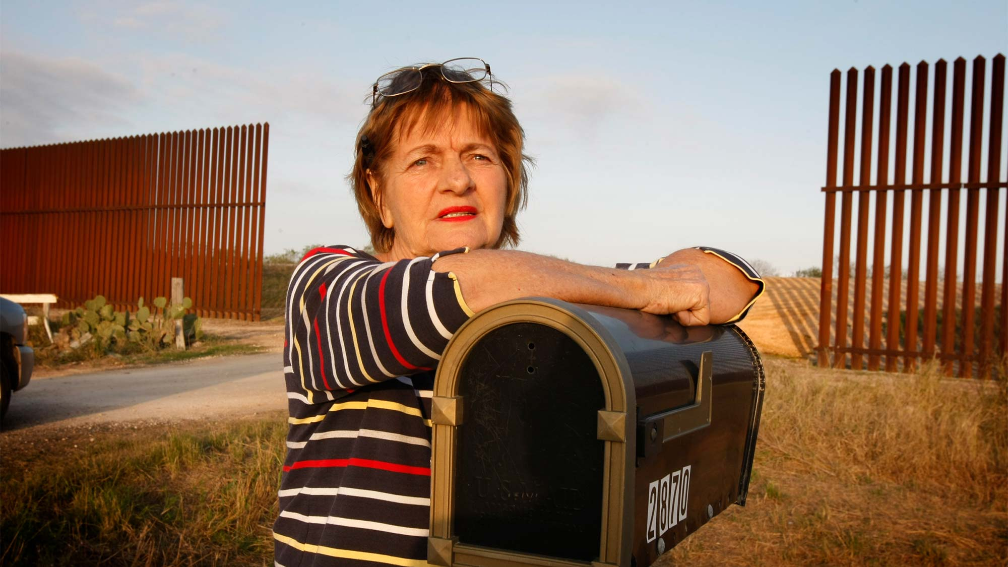 Outside of Brownsville, TX, Debbie Loop stands at the U.S./Mexico border fence that chops her property in half and divides her family's residences.