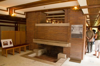 The fireplace separates the living room from the dining room in the open layout of the Robie House