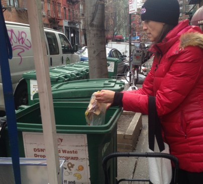 A New York resident empties a bag of food scraps into the compost bin at a greenmarket