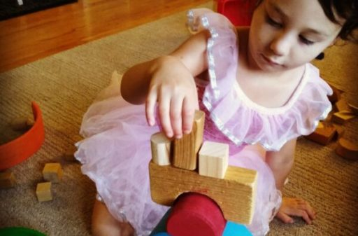 girl building with wooden blocks and Grimm's Rainbow