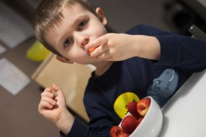 Child eating a bowl of fruit because he refused to eat what he was served.