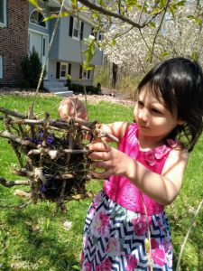 Child putting leaves into DIY Nesting Material Box.