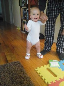 baby taking first assisted steps