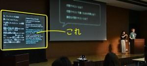 写真:登壇者(右手)の話した内容がステージ左手のスクリーンに字幕で投影されている。スクリーン左側に日本語、右側に英語の字幕。字幕用スクリーンが「これ」と強調されている。