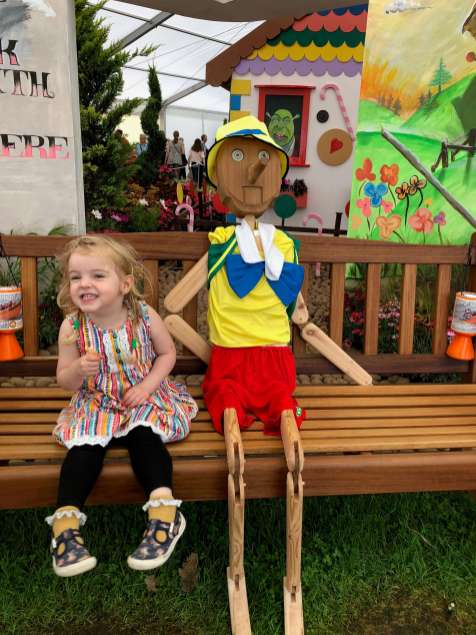 Spike sat on a bench at Southport Flower Show with Pinocchio from Shrek