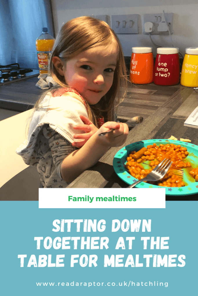 Pinterest graphic with blog title - Sitting down together at the table for mealtimes - and an image of Spike, a 4 year old blonde haired, brown eyed girl, eating beans and sausage at the table