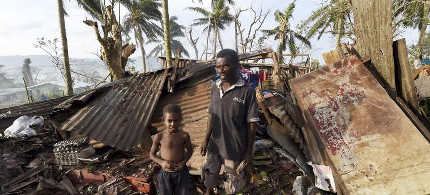Father and son in front of their home in Vanuatu. (photo: Reuters)