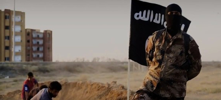 An Islamic State militant stands in front of an ISIS flag. (photo: Al Hayat Media)