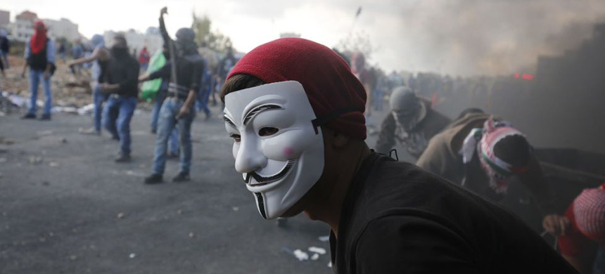 A man at a protest in a Guy Fawkes mask. (photo: Abbas Momani/Getty Images)