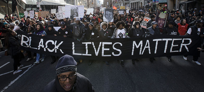 Demonstrators march in New York during the Justice for All rally and march in 2014. A year ago, grand juries had decided not to indict officers in the chokehold death of Eric Garner in New York and the fatal shooting of Michael Brown in Ferguson, Missouri. (photo: John Minchillo/AP)