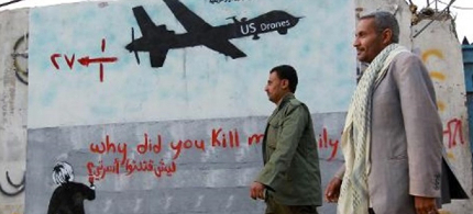 Yemeni men walk past a mural depicting a US drone and reading 'Why did you kill my family?' in Sanaa. (photo: AFP)