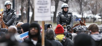Mounted police officer block protestors as they march, chant, shout and block intersections and stores along Michigan Avenue's Magnificent Mile' shopping area. (photo: EPA)