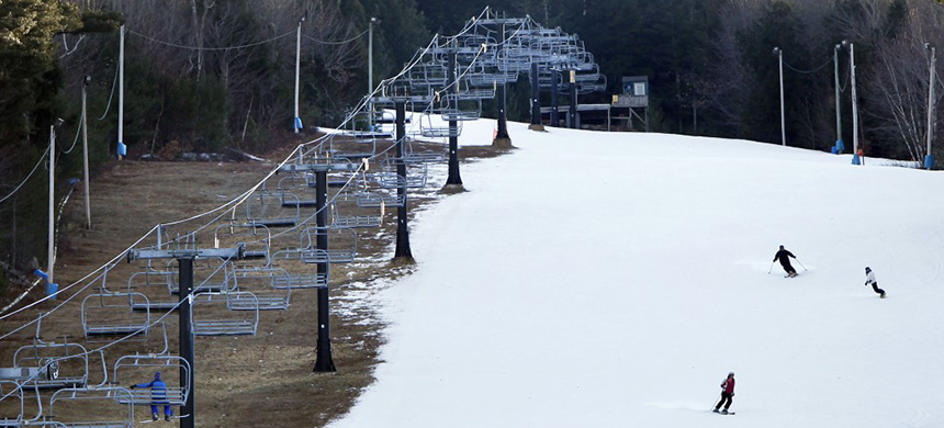 Man-made snow coats a ski run next to barren ground under a chairlift at Shawnee Peak ski area in Bridgton, Maine. (photo: Robert F. Bukaty/AP)