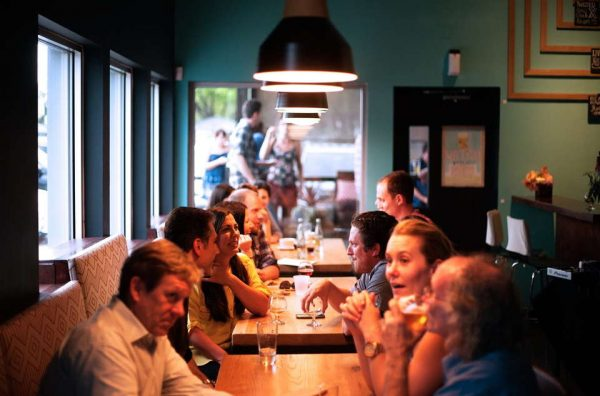 Picture of many people at multiple tables in a restaurant or coffee shop, holding lively conversations.