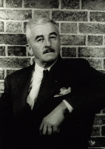 Photo of William Faulkner posing against a brick wall, by Carl Van Vechten