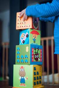 """Toddler's arm shown putting a block on top of three other colorful blocks. If you can see it, the word for it is """"concrete,"""" just like """"blocks."""""""