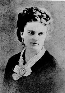 B & W Photo of Kate Chopin. Fair haired lady with hair coiled on her head, wearing a lace scarf pinned with a cameo.