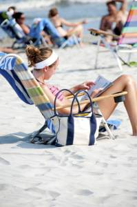 Girl in beach chair reading American short stories.