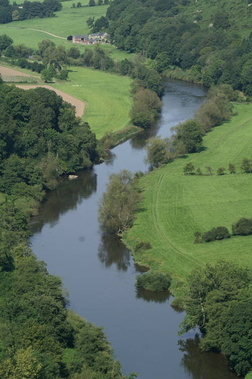 Aerial View of Wye River near Tintern Abbey winding between green fields.