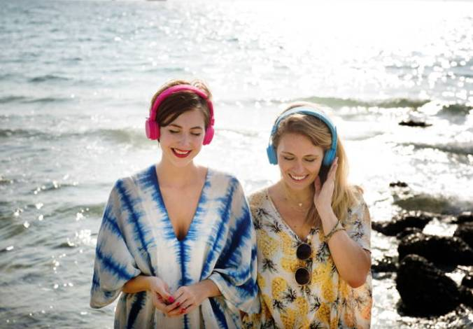 Two young women wearing headphones stand with their back to the ocean.