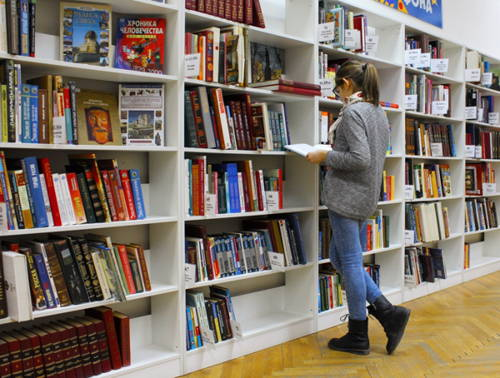 Young woman standing and reading near bookshelves in store.