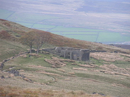 Color photo of remains of Top Withens on the Moor near Haworth, possible inspiration for Bronte's Wuthering Heights. House has walls but no roof, set overlooking a wide sweep of moors far below.
