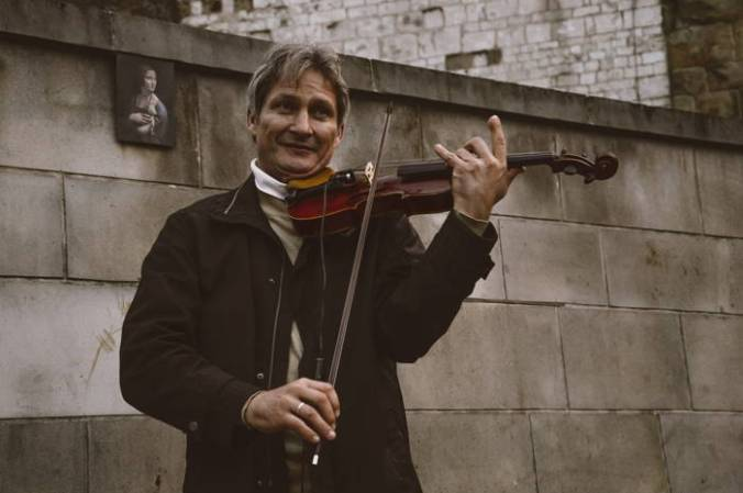 His own style: Man wearing casual jacket and turtleneck playing violin outdoors in front of stone wall, with Vermeer print on wall behind him.